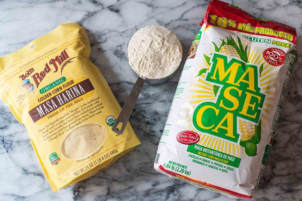 A bag of Bob's Red Mill Masa Harina and a bag of Maseca Instant Yellow Corn Flour. A measuring cup is filled with corn flour is between the bags.