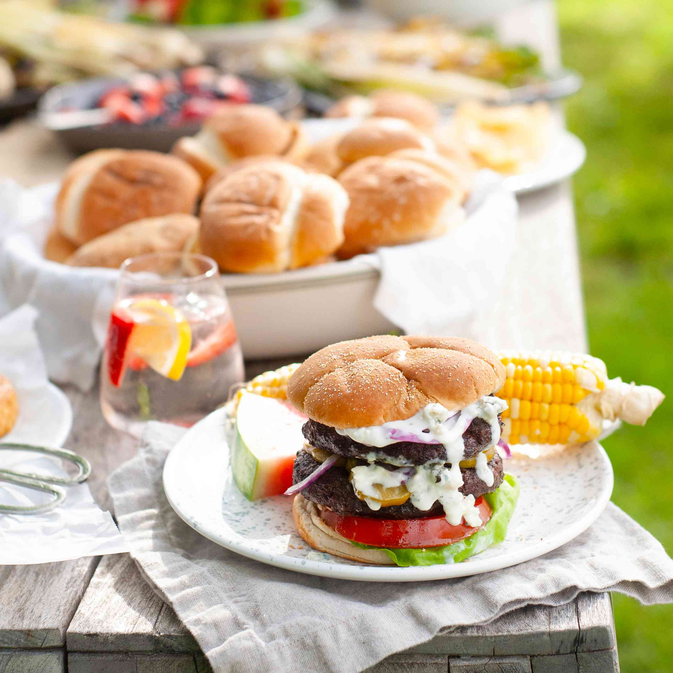 A picnic table filled with buns, drinks, watermelon. A plate in the front of the table has a hamburger on it, with blue cheese sauce dripping down the front. An ear of corn with a slice of watermelon is also on the plate.