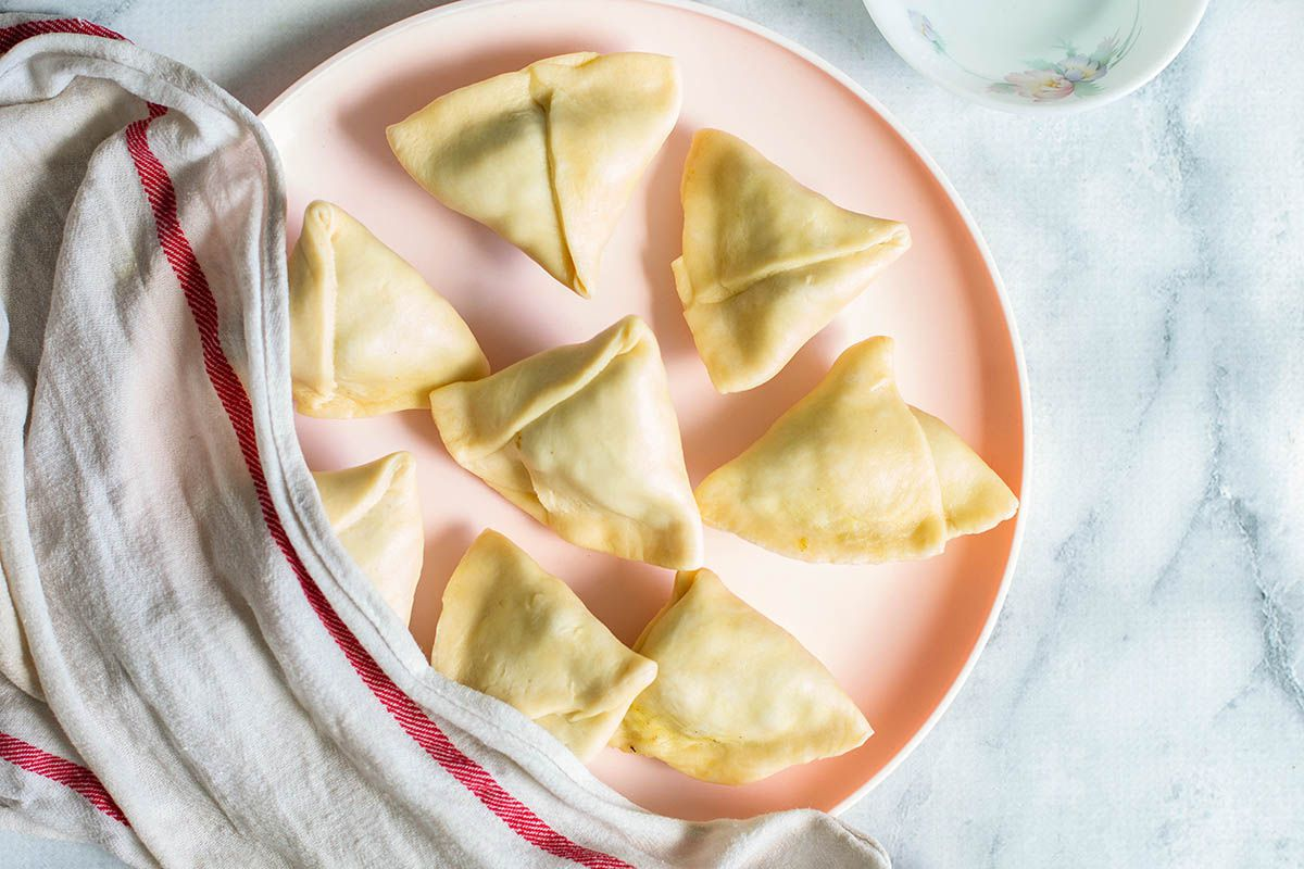 Pink plate with raw vegetables samosas.