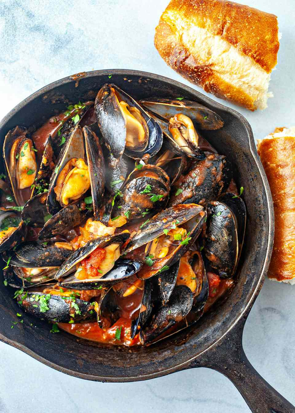 Steamed Mussels in Tomato Sauce - mussels in cast iron pan with baguette