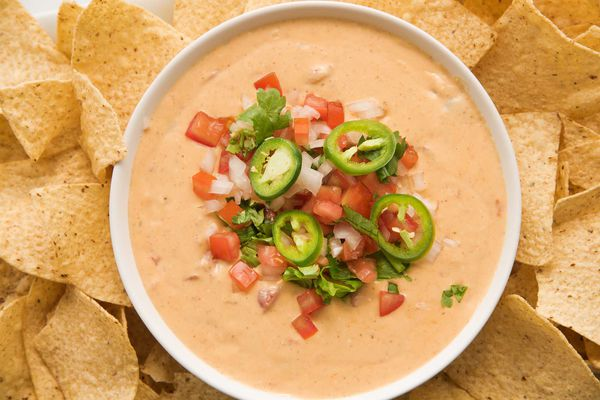 Get ready for game day with a bowl of ceamy queso dip topped with pico de gallo and surrounded by tortilla chips