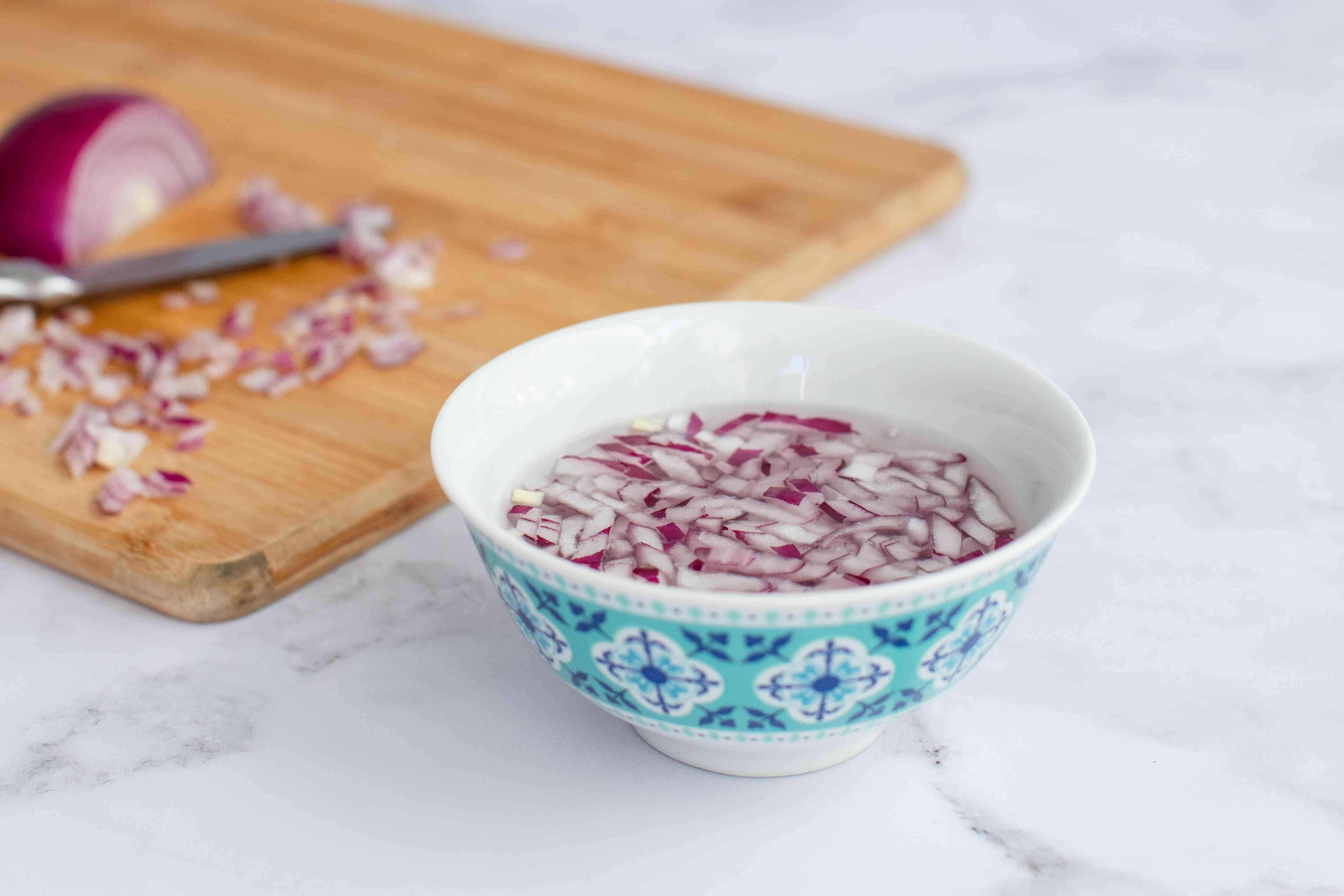 Chopped red onion in a bowl of liquid to make a green bean salad recipe.