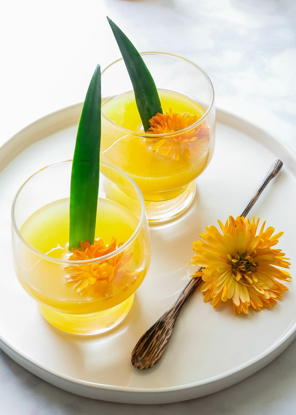 A white tray has two glasses of cava mimosa with an orange flower an d green pineapple leaf decorating each one. A stir stick and a third flower is on the tray.