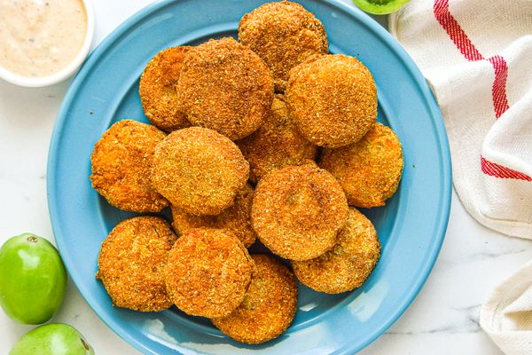 Overhead view of a plate of green tomatoes that have been breaded and fried.
