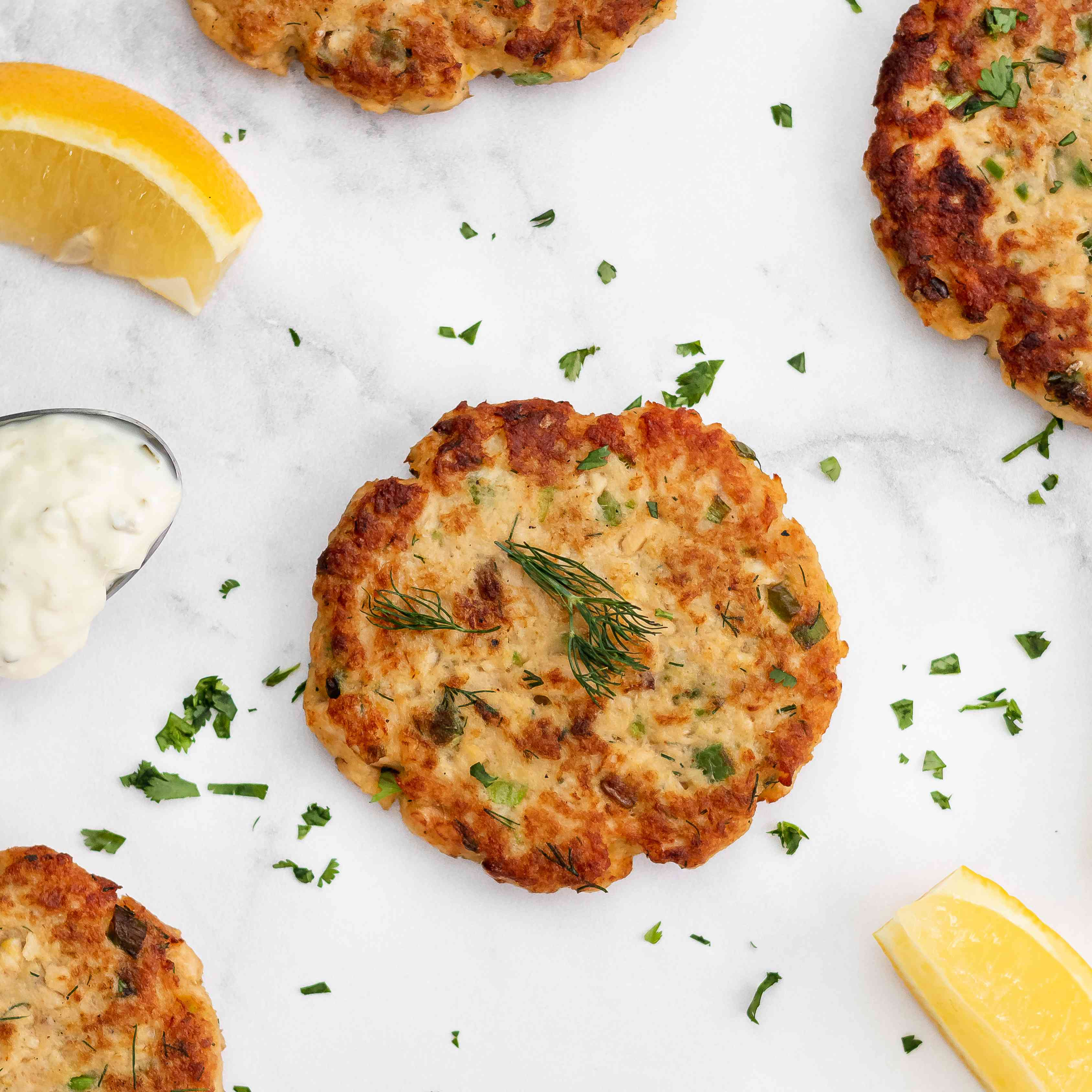 Salmon patties on a white background with a dip and lemon wedges.