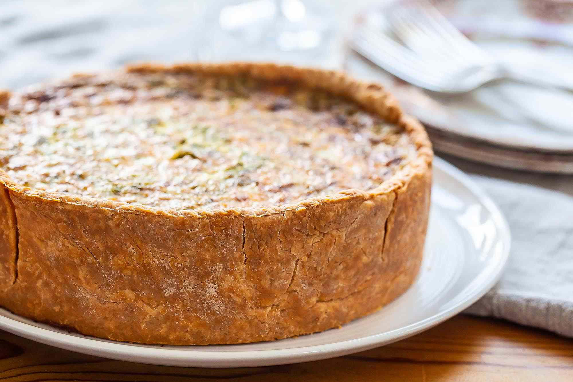 A mile high quiche is on a white platter. The crust is golden brown as is the filling. Partial view of plates and forks to the upper left of the quiche.