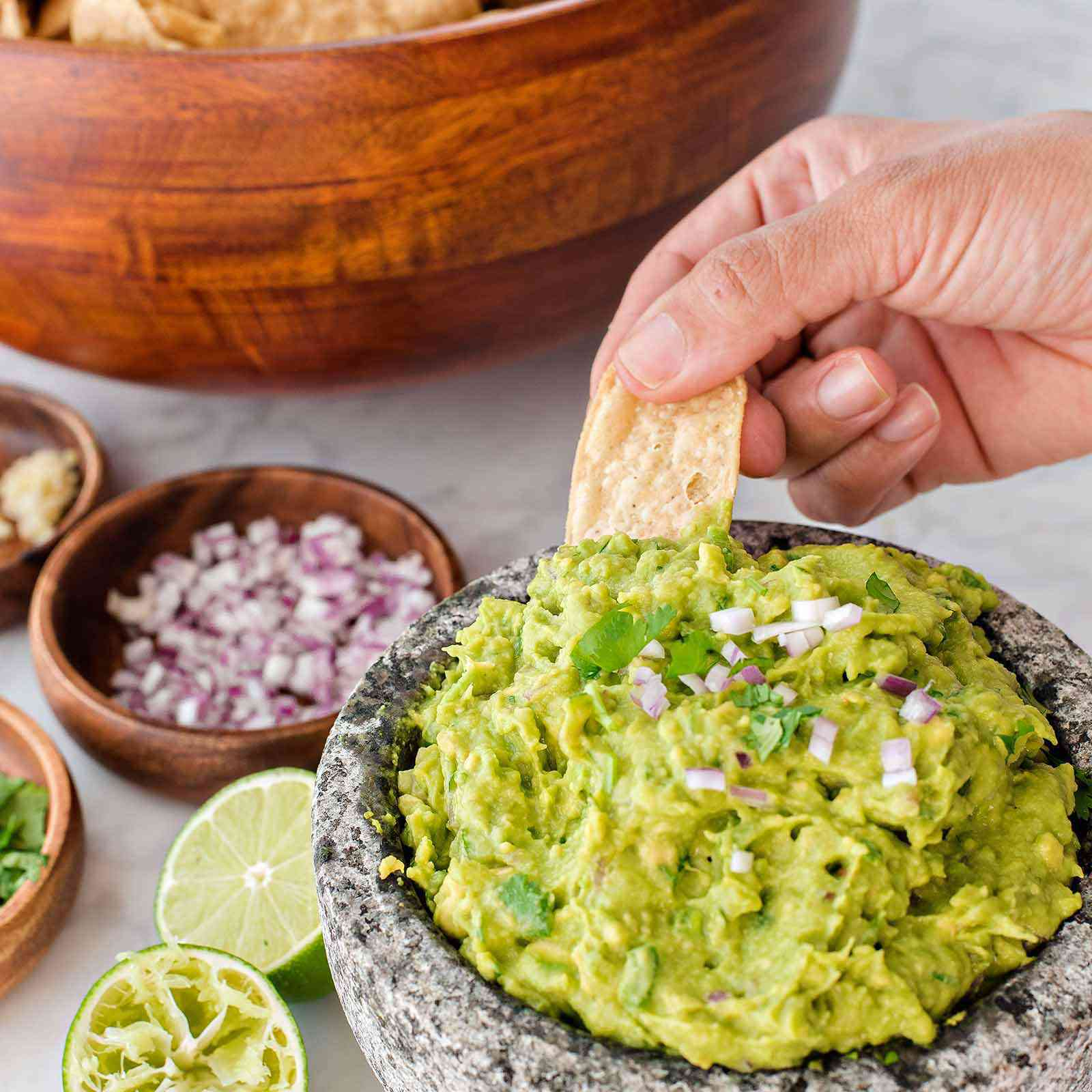 How to Make Guacamole - guacamole in a bowl with someone dipping a chip into it