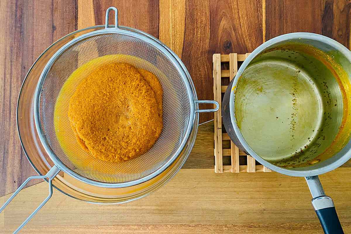 Ground turmeric in a strainer with a pot set next to it to make a Tumeric and Ginger Elixir.