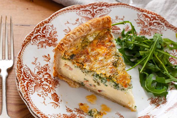 A slice of best deep dish quiche on a decorative china plate. A handful of arugula is to the right of the quiche. A fork is to the left of the plate and a table linen is above the plate.