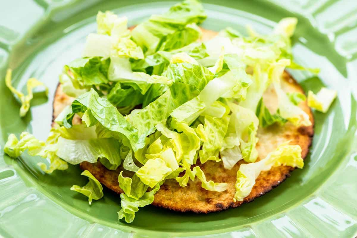 How to Make Tostadas pile on the lettuce