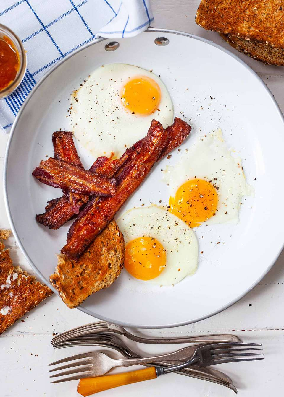 Over easy eggs on a plate with a side of bacon.