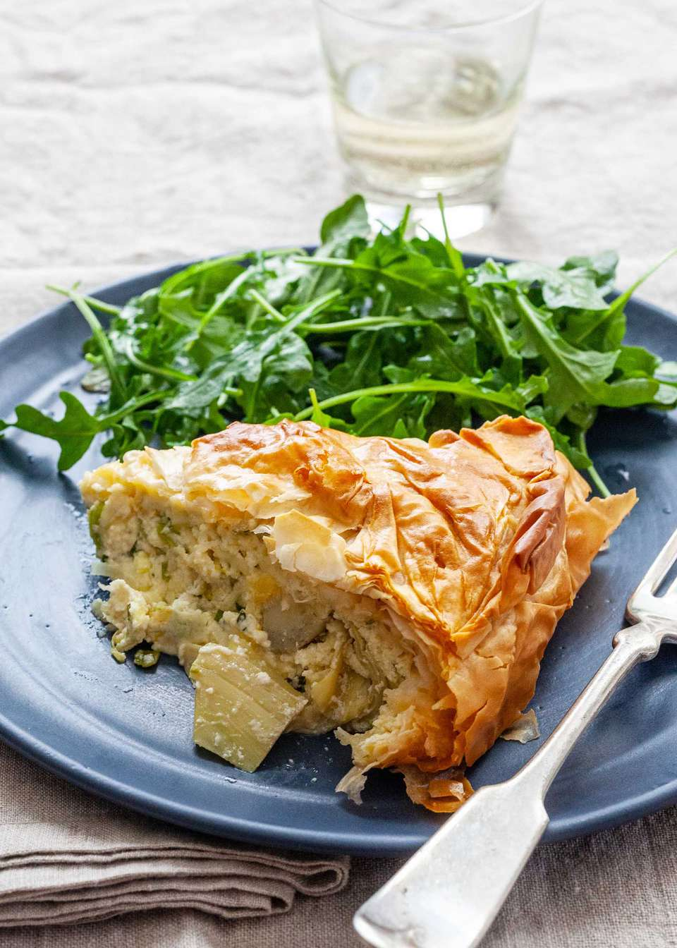 Side view of a slice of spring pie on a blue plate with a golden, flaky crust and topping. Chopped artichokes are visible in the cheesy filling. A bright arugula salad is behind the pie on the plate. A glass of white wine is behind the plate. Linens are under the plate and a fork is set to the right of the pie on the plate.