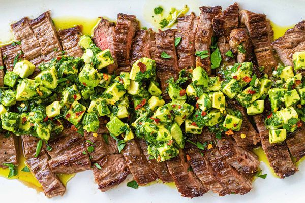 Quick and Easy weeknight skirt steak sliced across the grain and covered with avocado chimichurri on a white plate