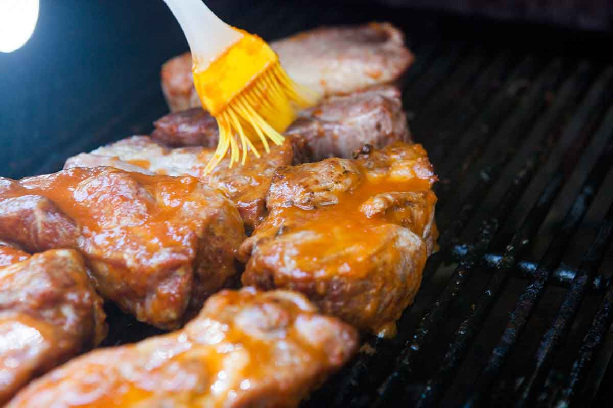 brushing sauce over country ribs cooked low and slow