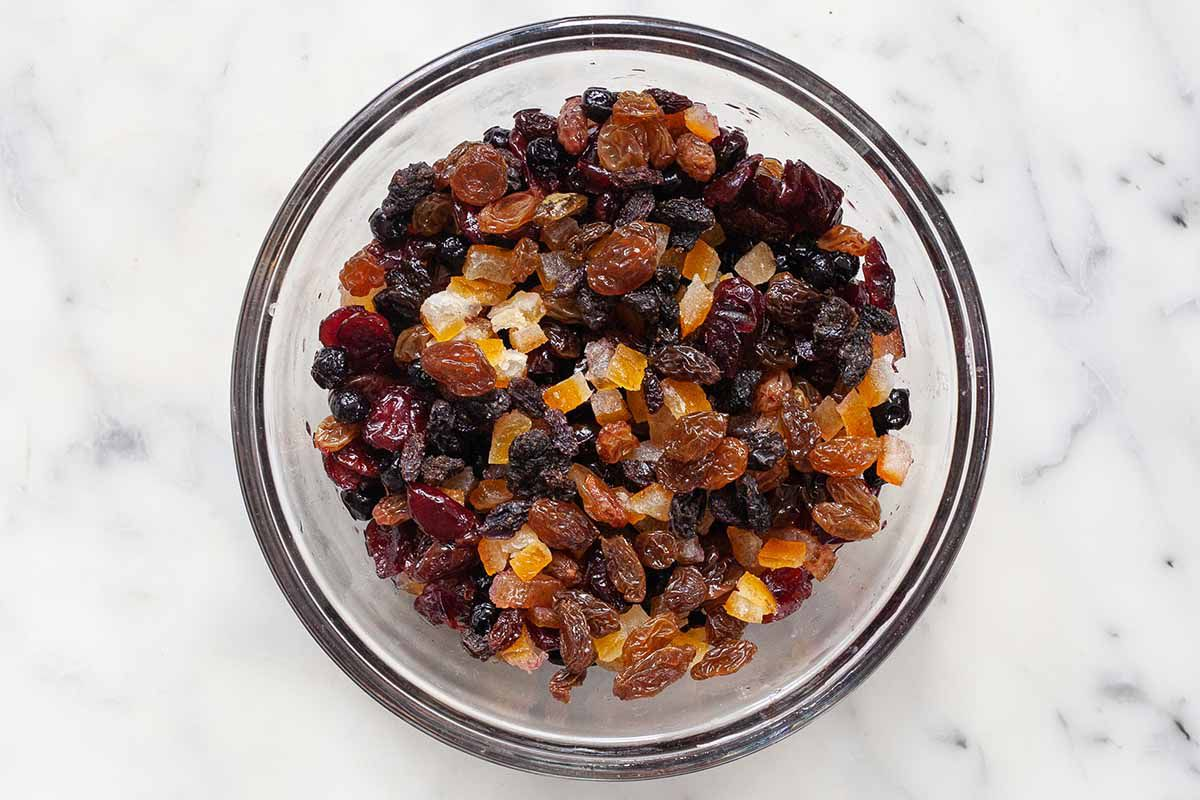 Mixed dried, rum-soaked fruit for German Stollen Christmas bread in a glass bowl.