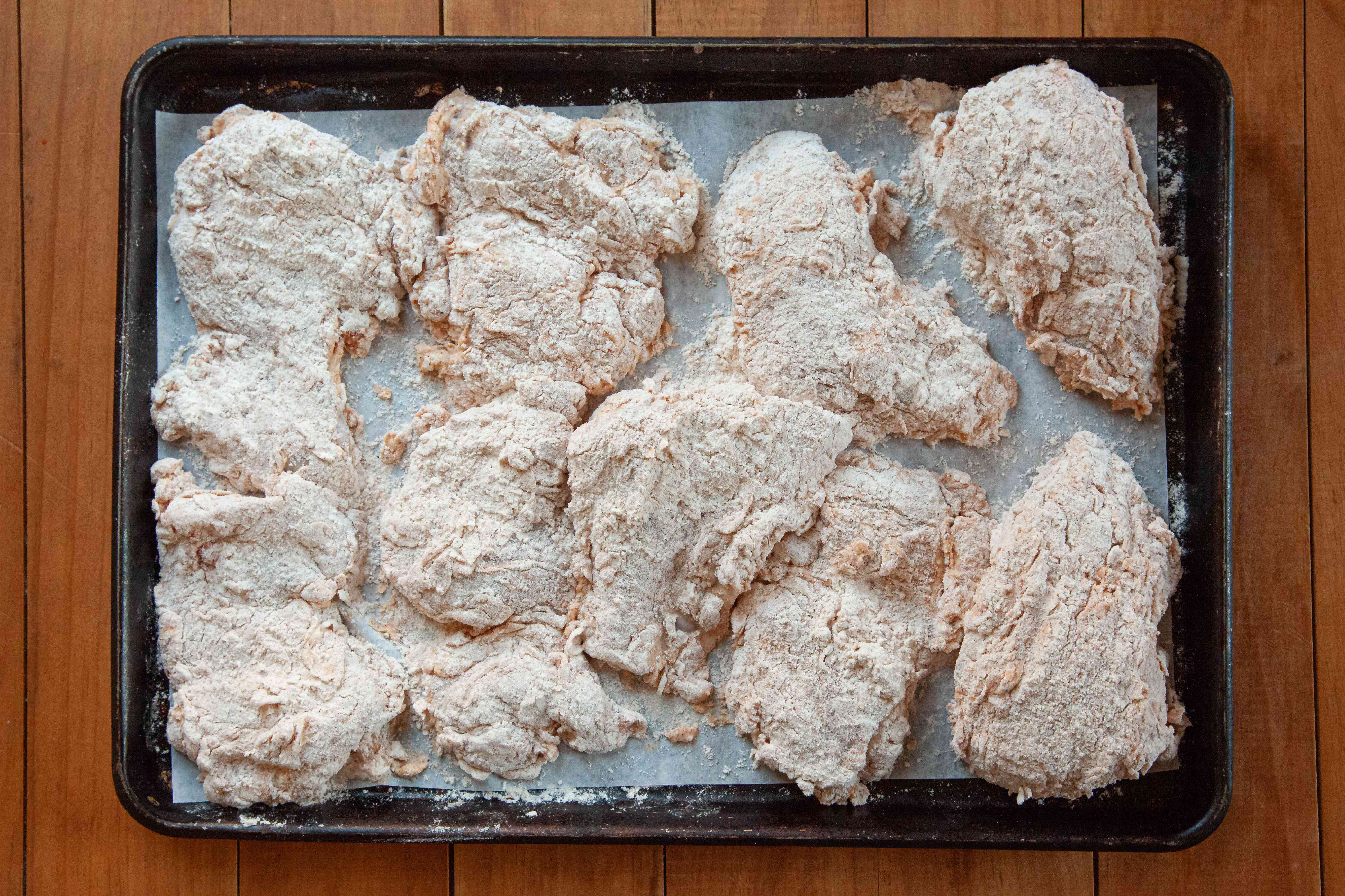 Breaded chicken on a baking tray to make Nashville-style hot chicken.