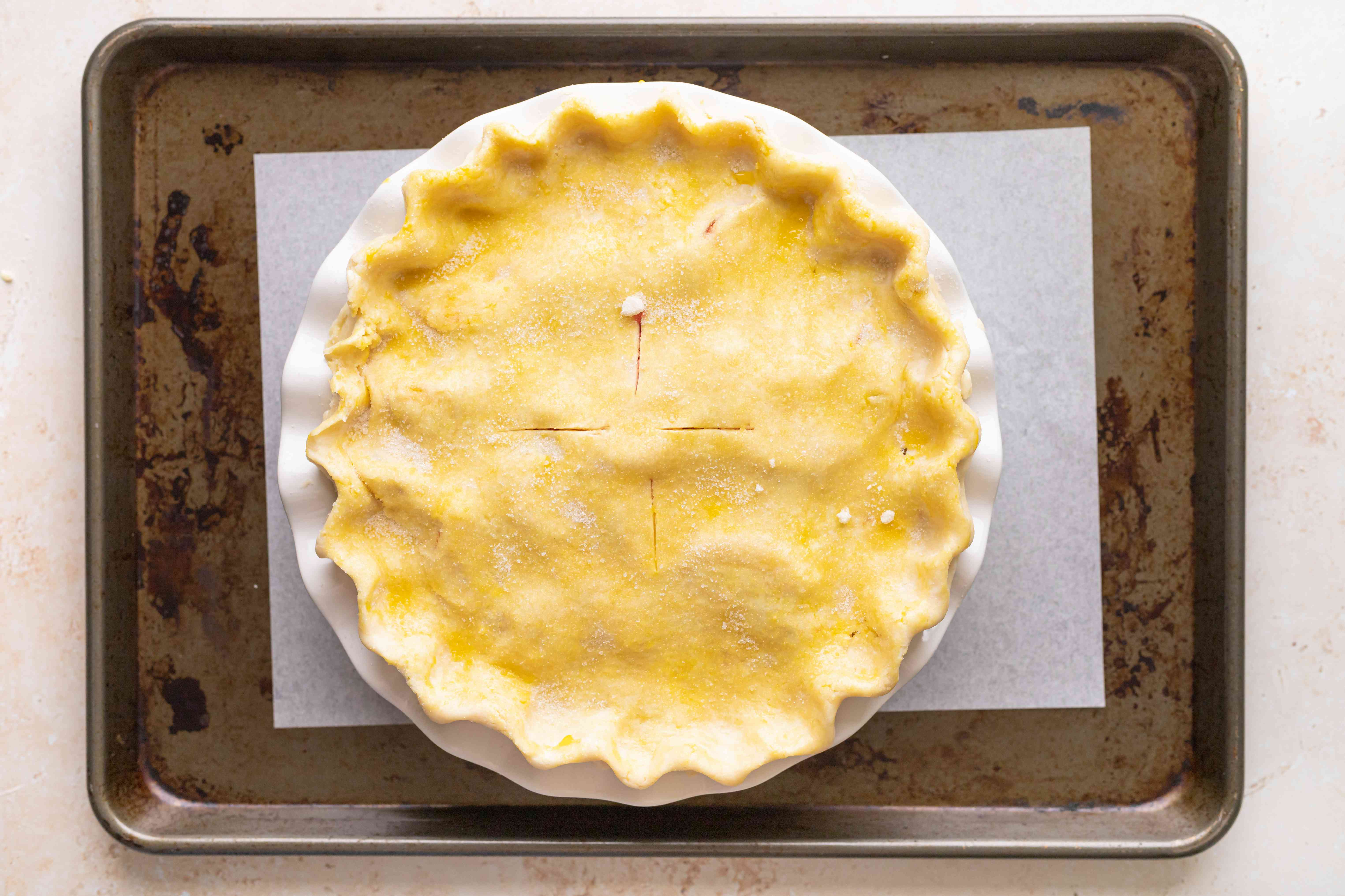 A stone fruit and berry pie on a baking sheet before baking.