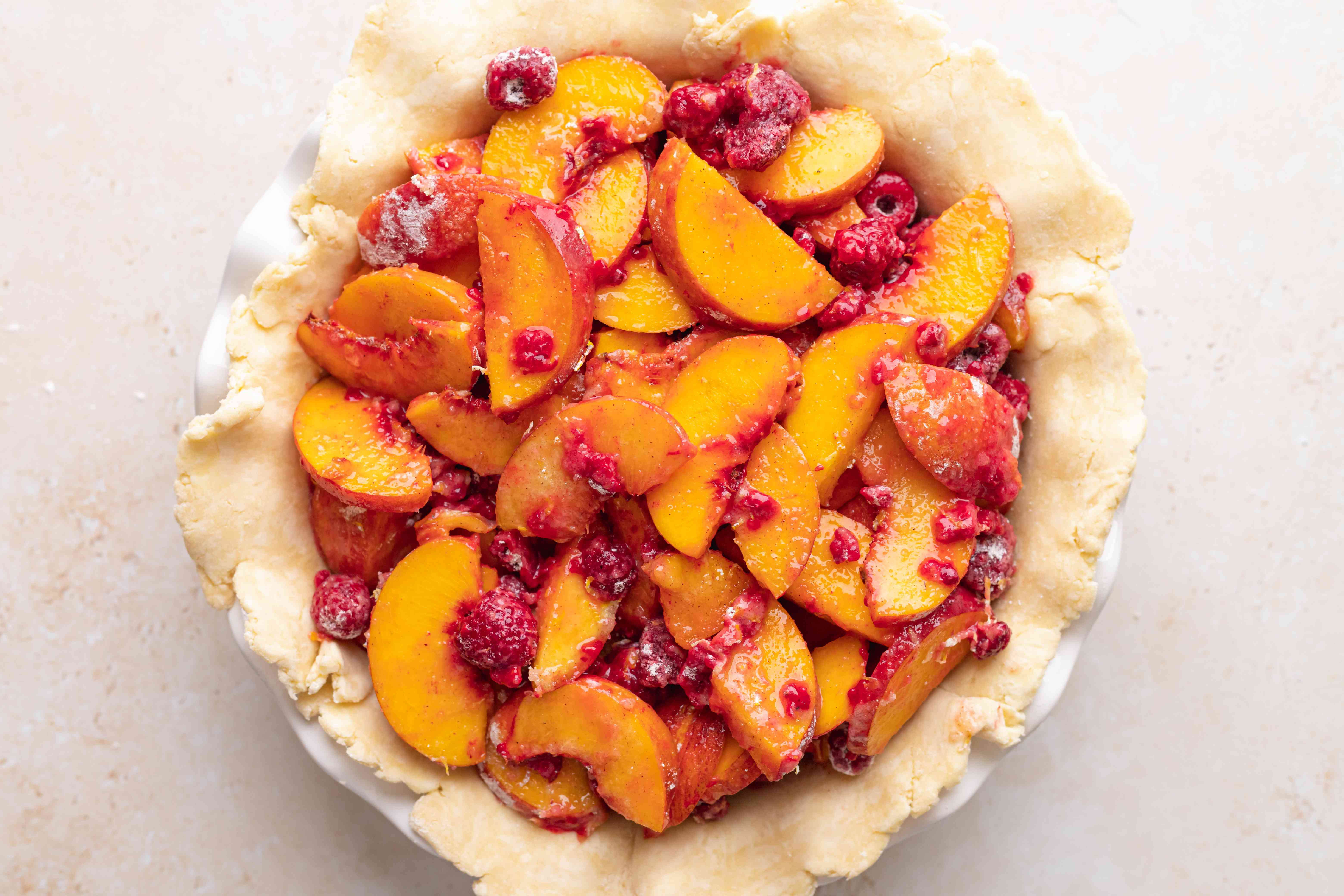 A pie crust filled stone fruit and berry filling to make a pie