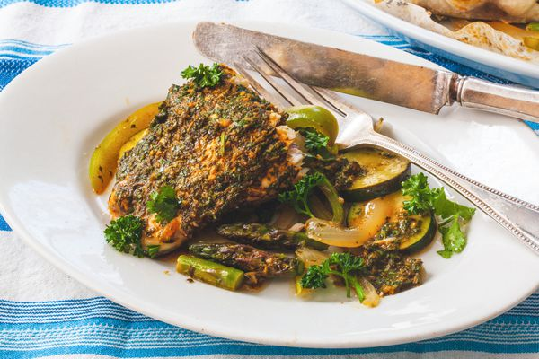 Parchment Baked Fish with Chermoula sauce on a plate with a knife and fork.