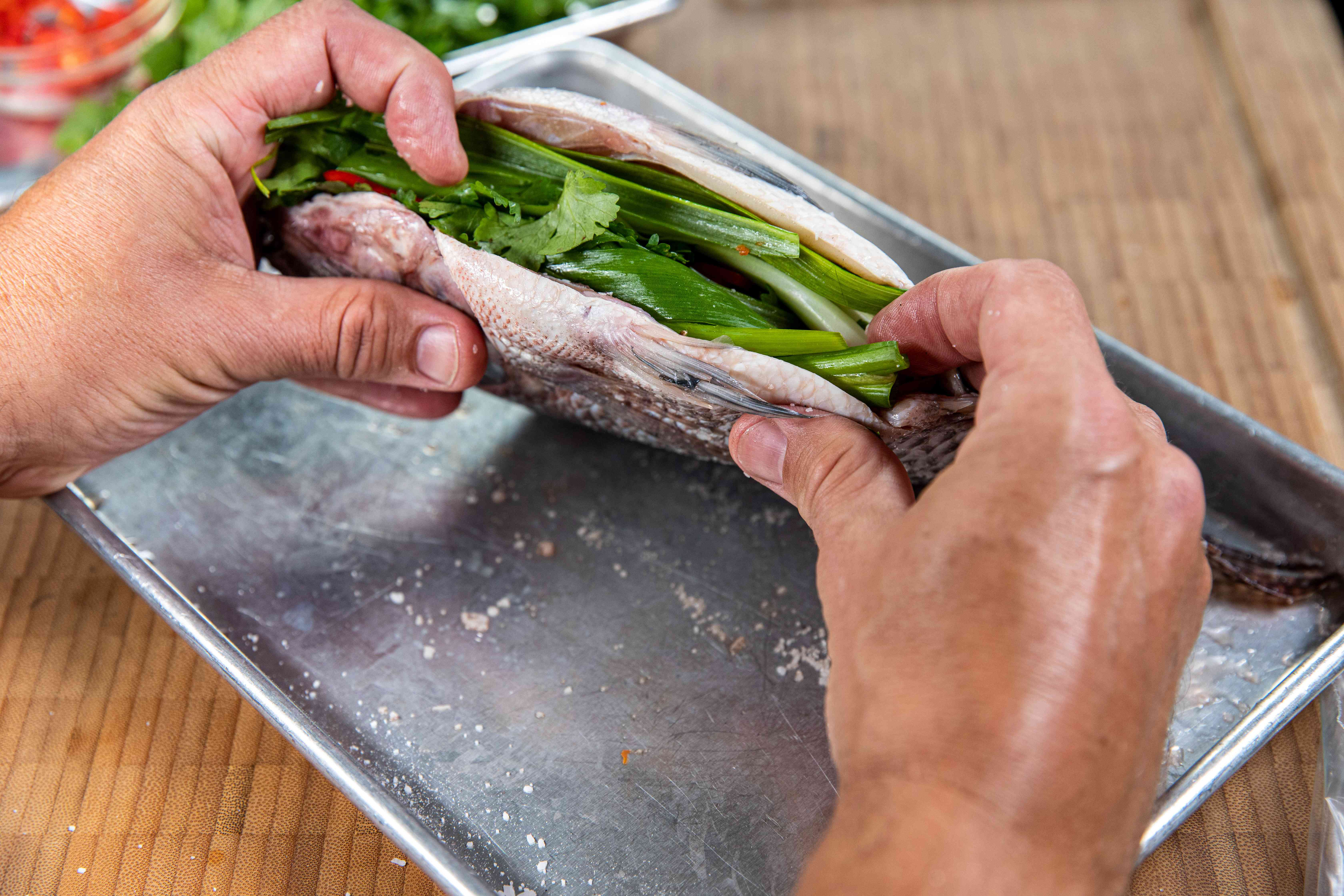 Filling the fish cavity with herbs for a grilled tilapia recipe.