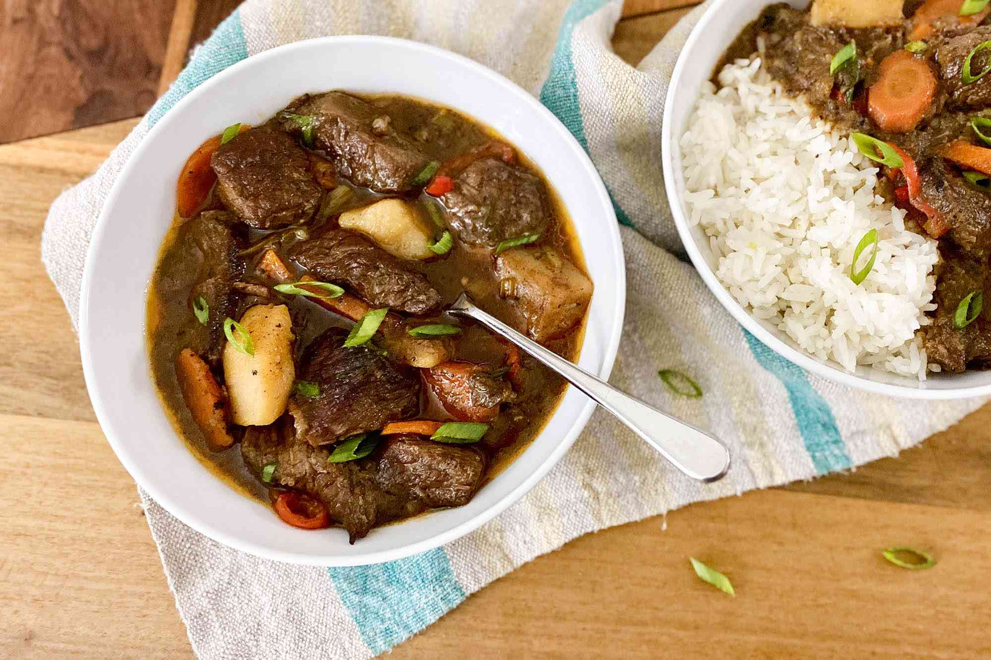 Jamaican Stewed Beef in two bowls and served with rice.