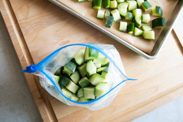 Chopped zucchini in a freeze bag on a wood cutting board