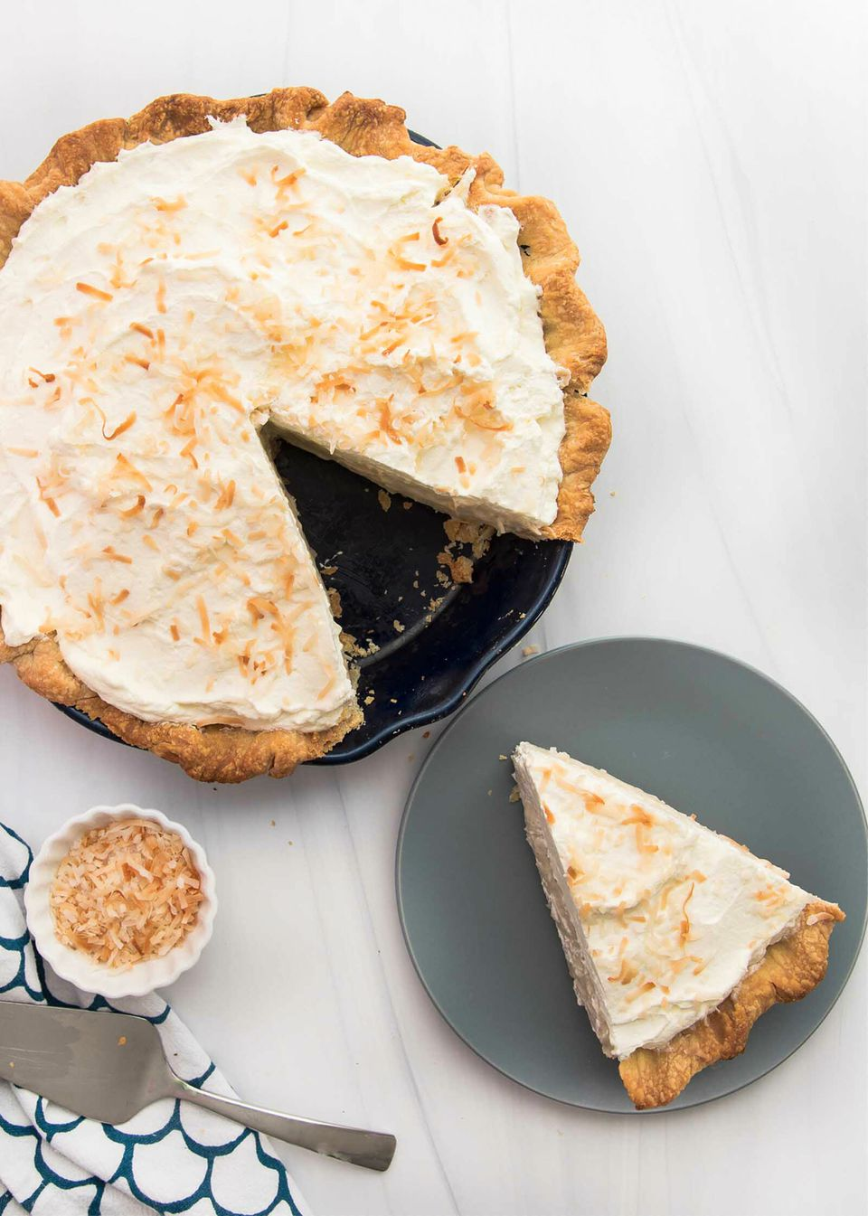 Overhead view of the best coconut cream pie with a slice removed and set on a plate.
