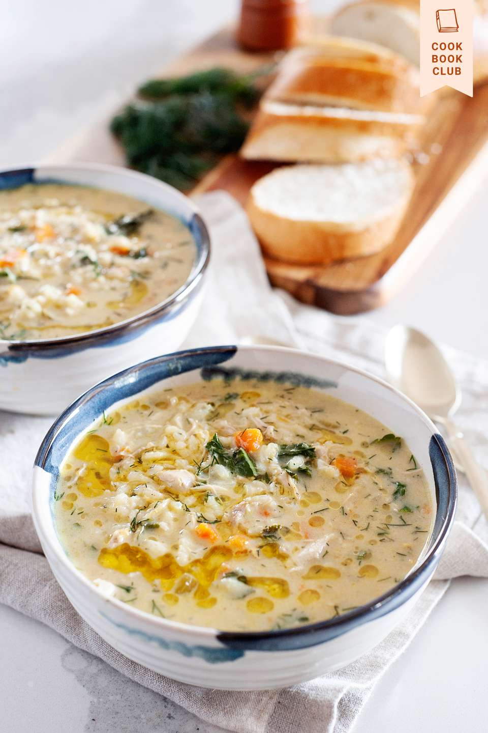 Avgolemono in a bowl with a second bowl and sliced bread behind it.
