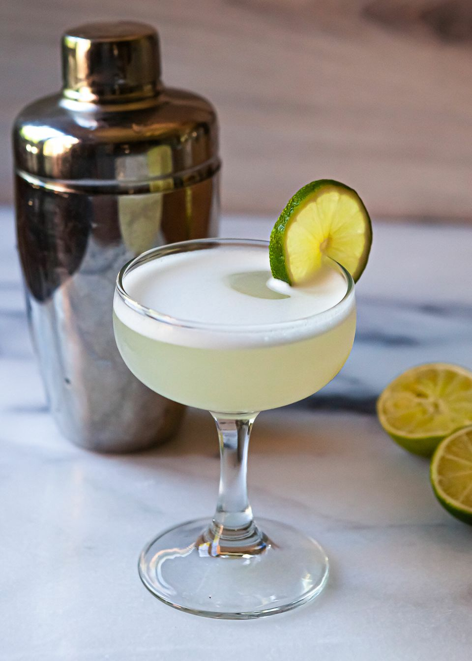 A gimlet recipe in a chilled coupe glass with a cocktail shaker behind it and limes to the right.