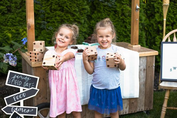 Two girls holding yard dice for backyard family activities.