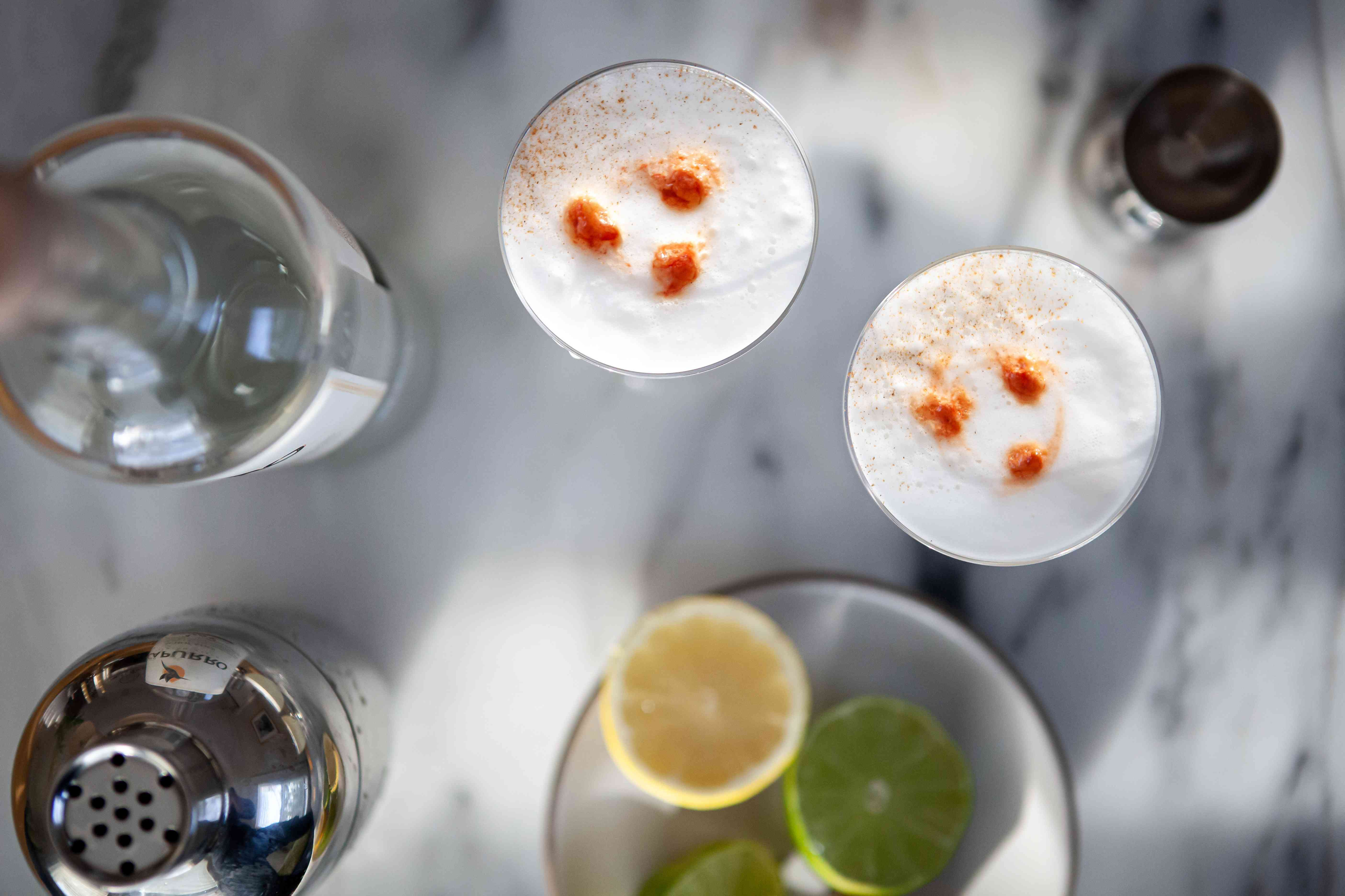 Overhead view of two Pisco Sour Cocktails on a marble countertop and garnished with three drops of bitters.