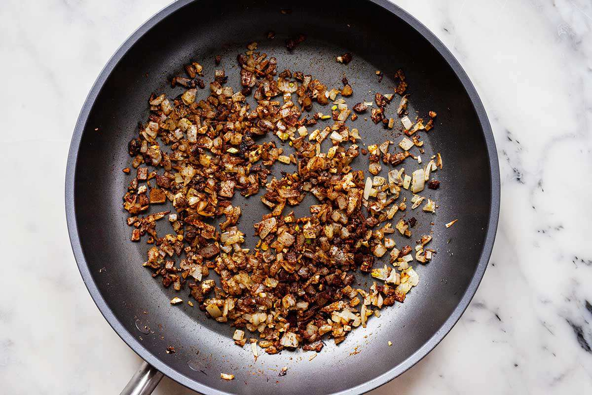 Caramalized chopped onions in a saute pan on a marble background.