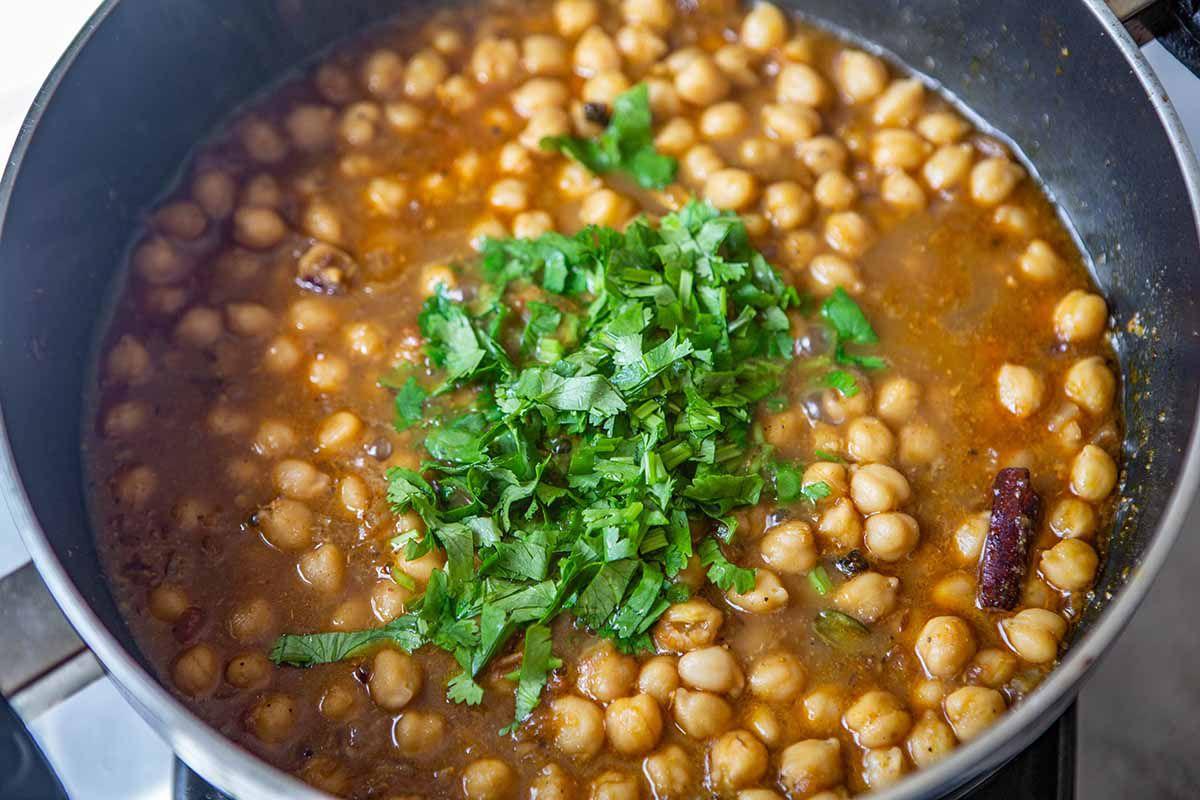 Easy Chana Masala Recipe - - chickpeas in spicy liquid with fresh, green herbs.