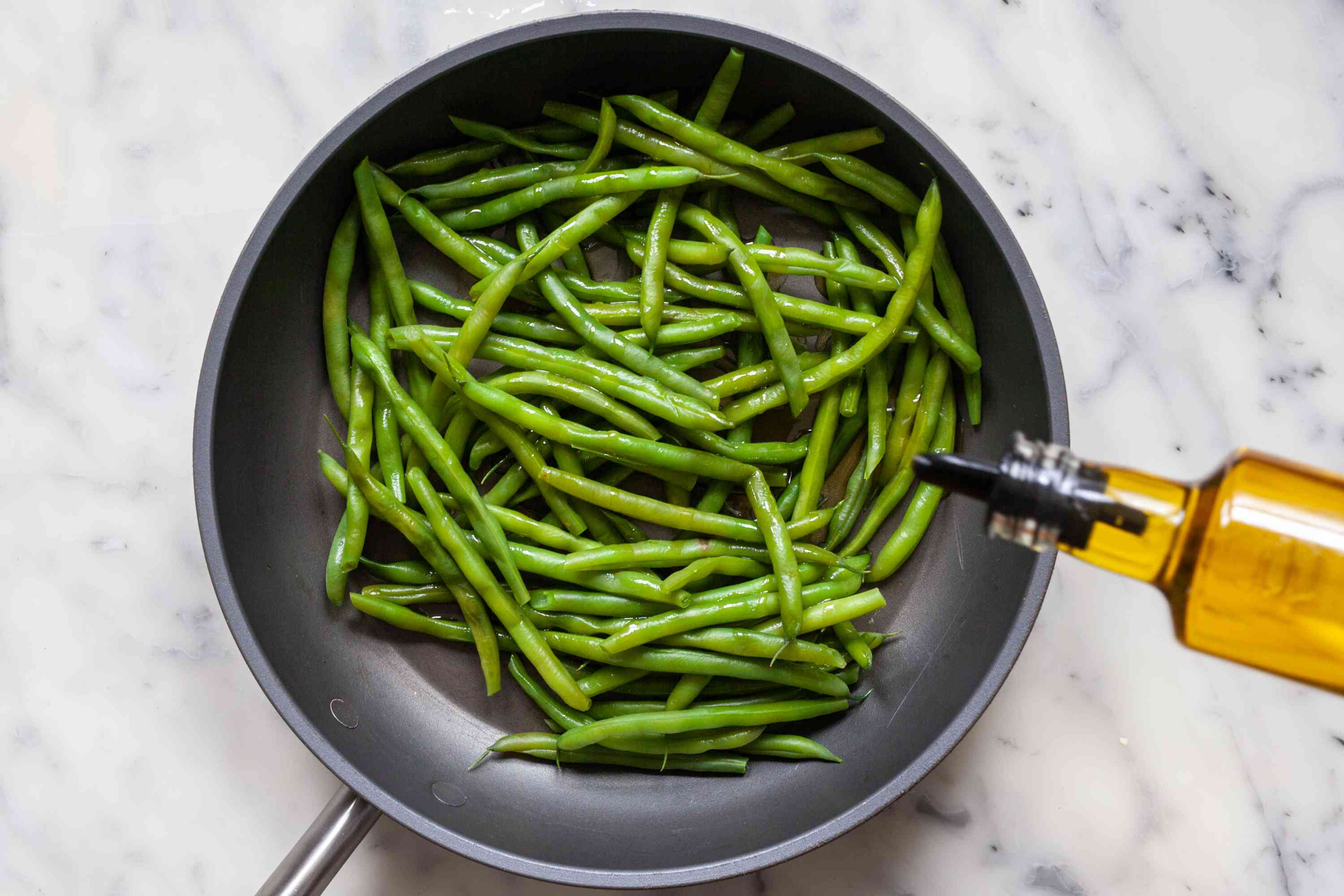 Adding oil to green beans to make Blistered Green Beans with Gochujang.