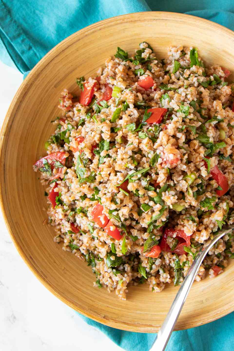 Tan bowl with tabbouleh and a spoon.