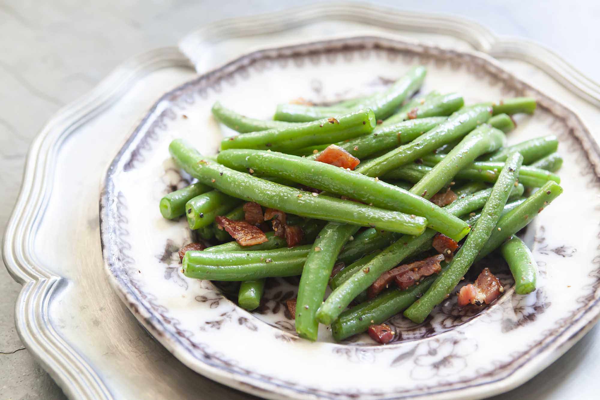 Side shot of fresh green beans, blanched and sauteed with bacon on a plate