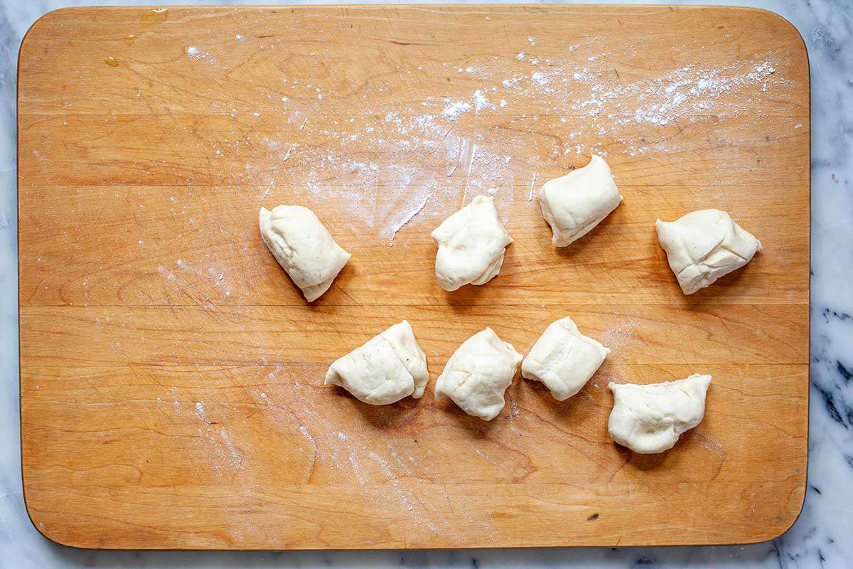 Dough for easy homemade flour tortillas is separated into eight equal pieces on a wooden cutting board.
