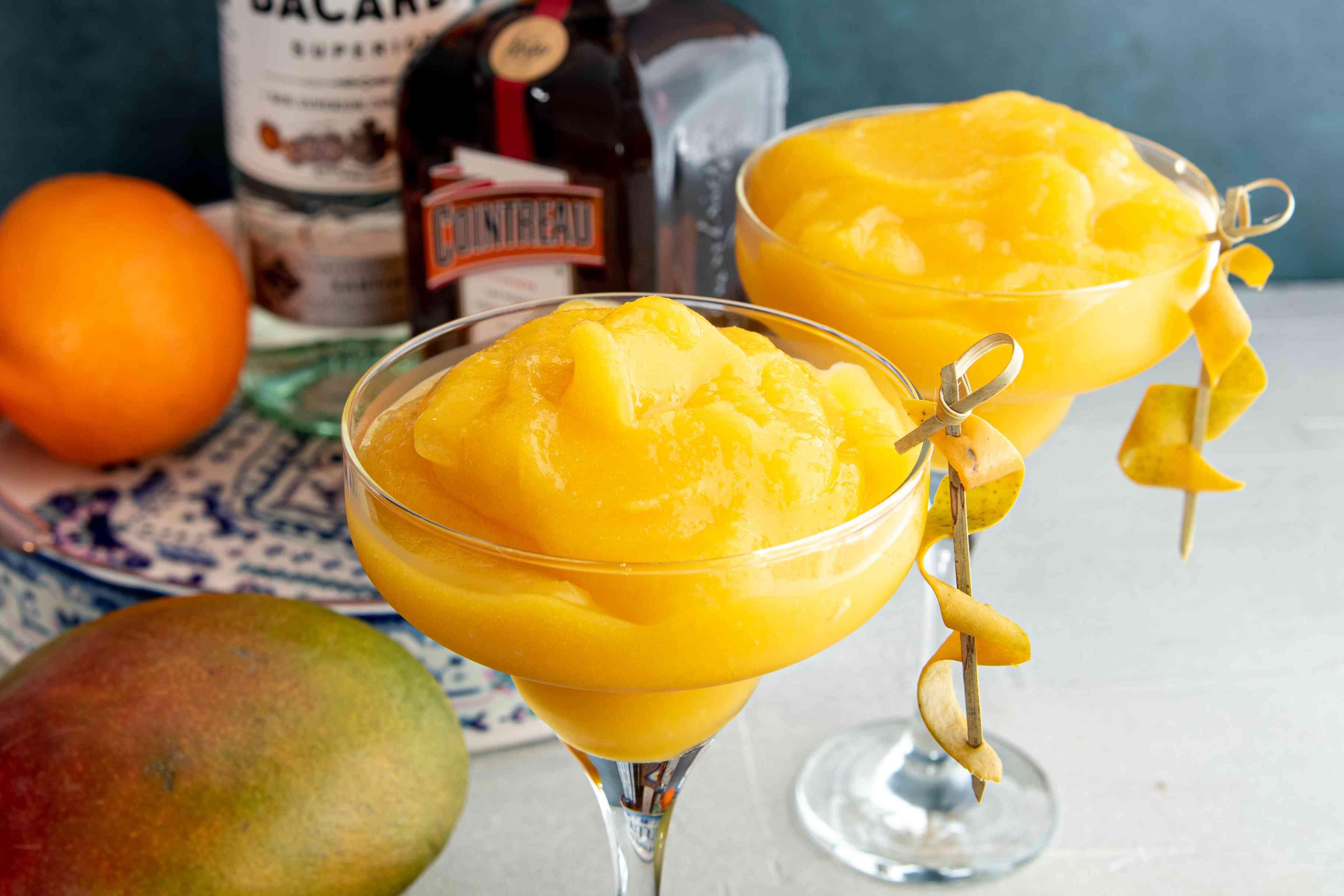 Frozen mango daiquiris in martini glasses garnished with curled mango peel.