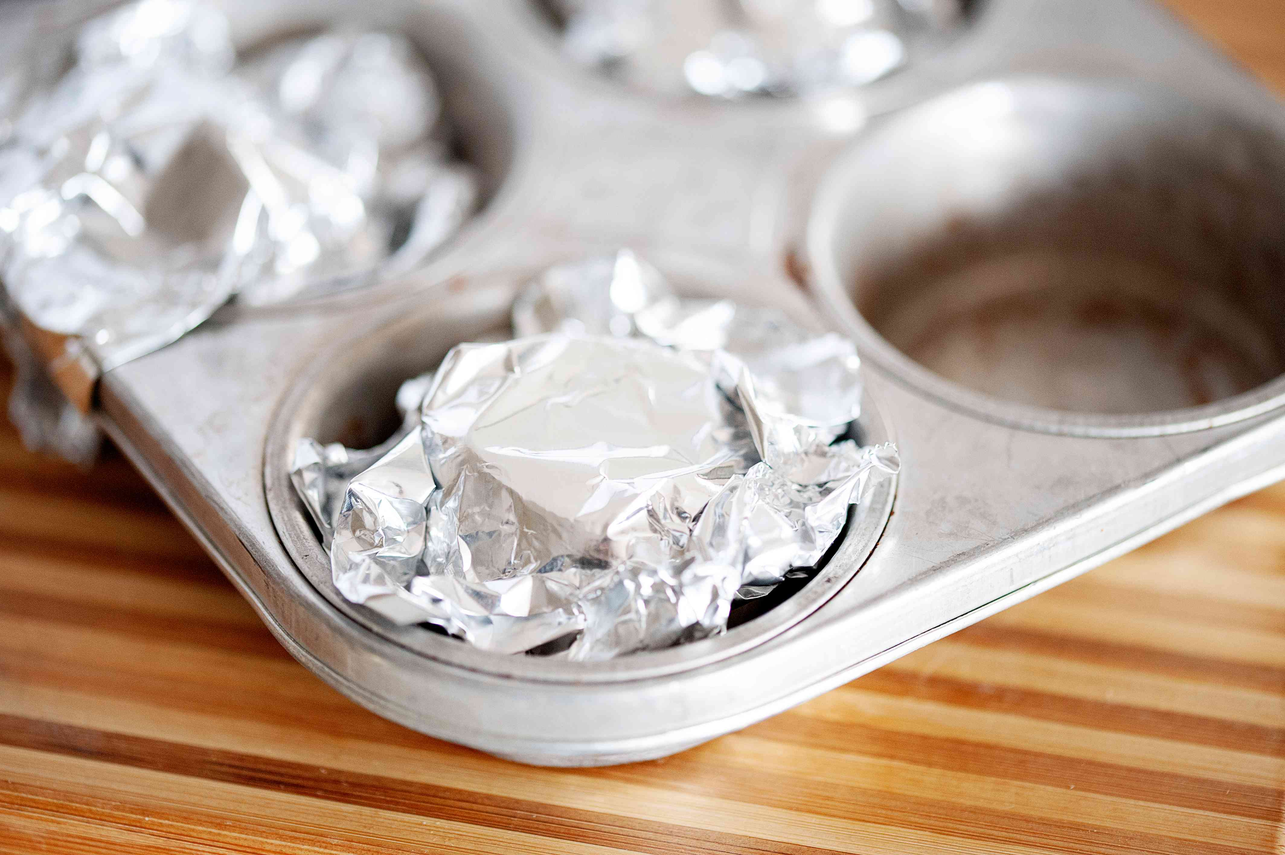 Foil wrapped head of garlic in a muffin tin.