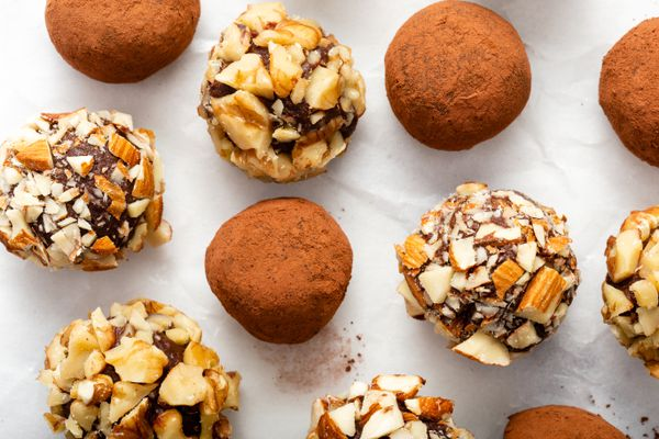 Overhead view of chocolate truffles covered in cocoa and chopped nuts.
