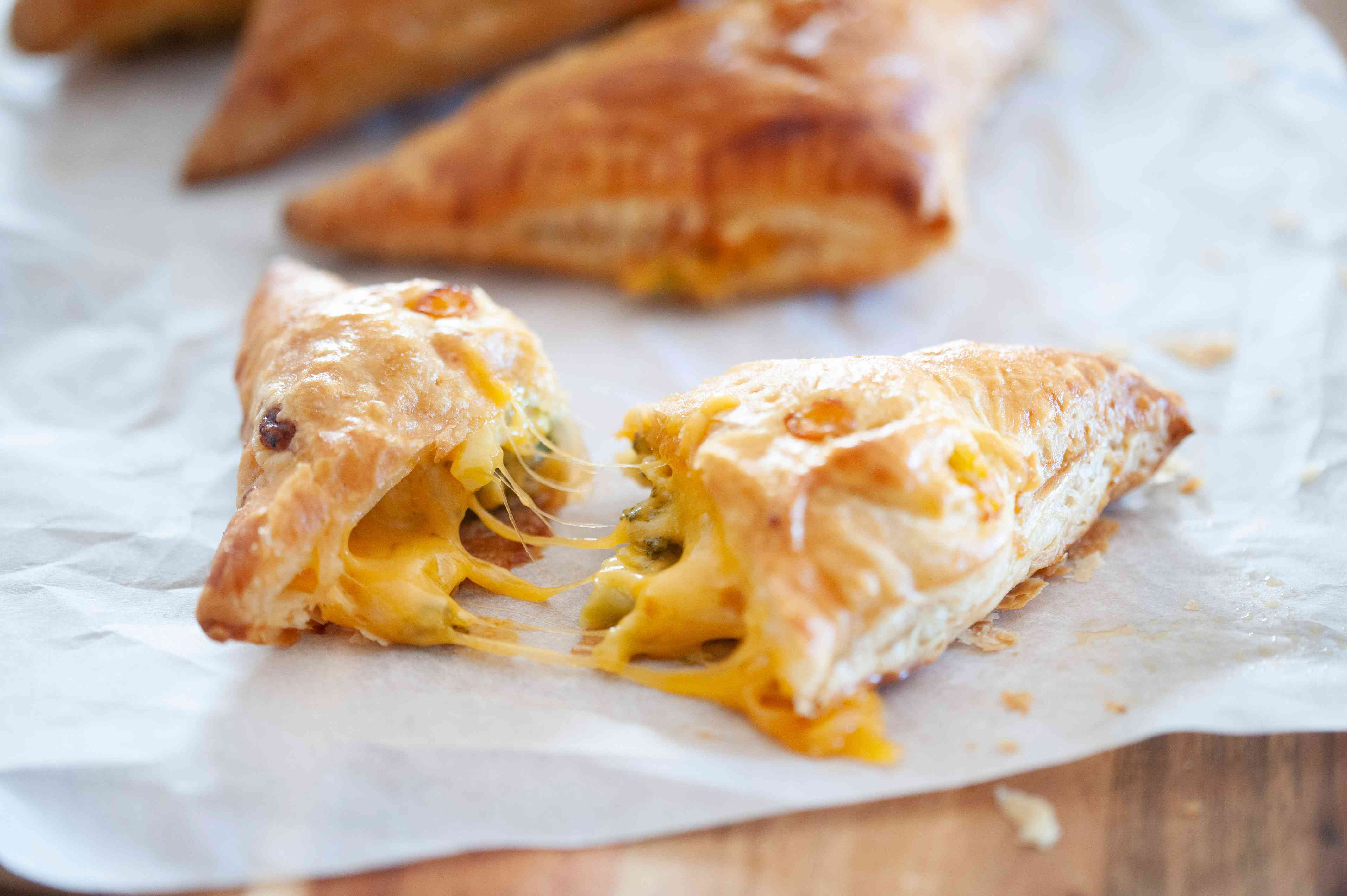 Broccoli and cheese hand pies on parchment paper with one split open to show the melted cheese and broccoli.