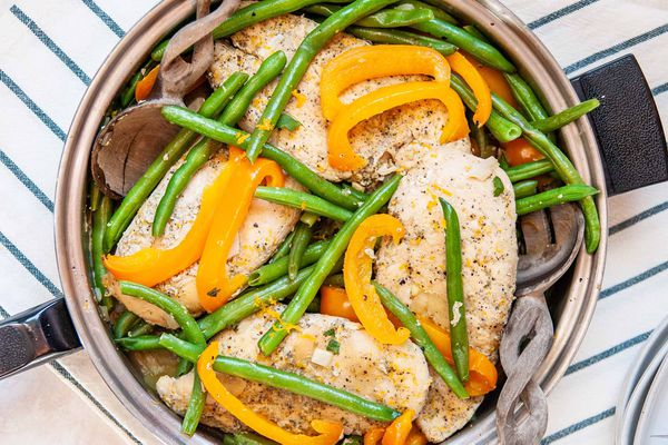 Skillet Chicken Dinner Recipes-close up of chicken in a skillet with green beans and orange bell peppers with wooden serving spoons on the side.