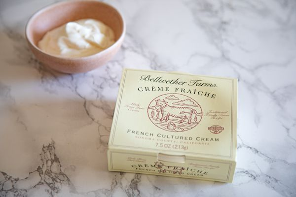 A bowl of Crème Fraîche with the packaging set in front of it.