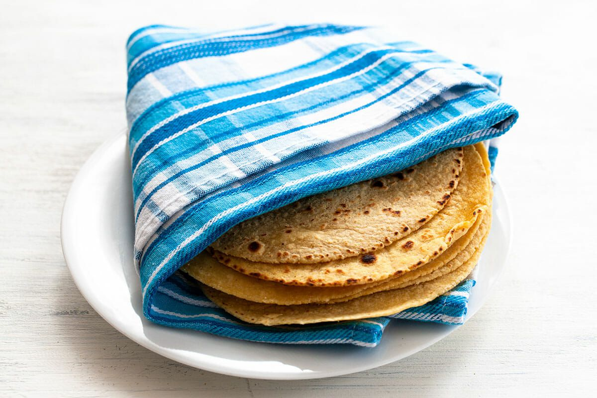 Corn tortillas wrapped in a kitchen towel for easy fish tacos.