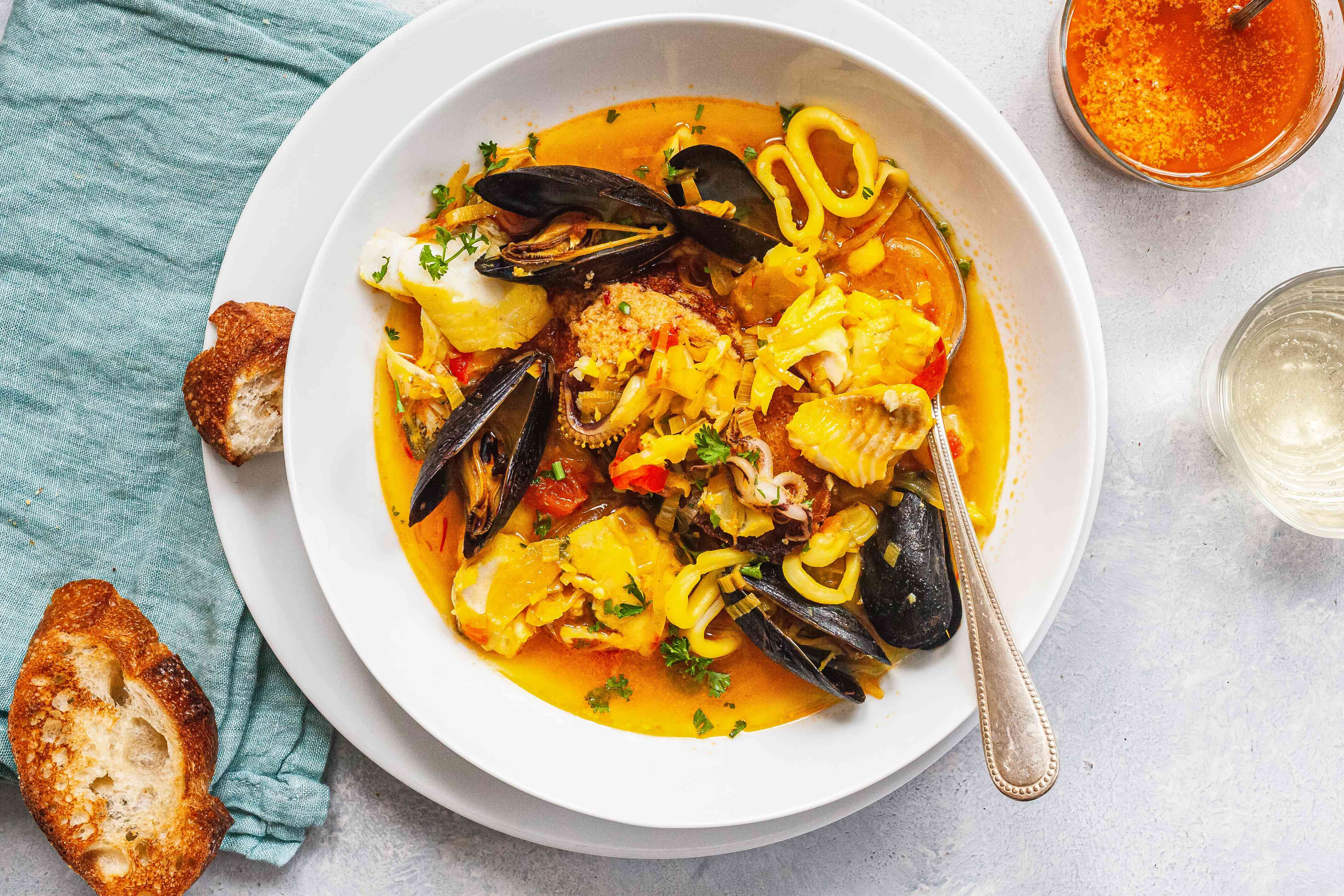 Overhead view of a bowl of bouillabaise and sliced bread.