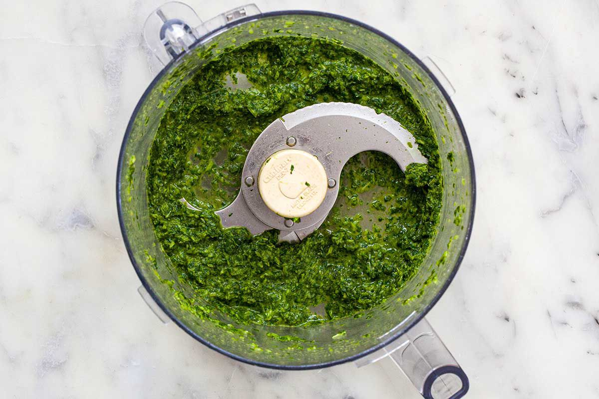 Bowl of a food processor on a marble background. Cilantro and olive oil are pureed to make lentil burgers with chutney.