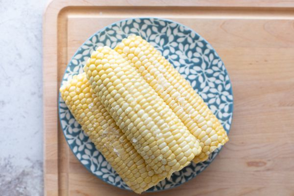 Three ears of cooked corn on the cob on a blue flower plate