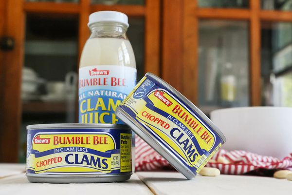 Two cans of clams and a bottle of clam juice on a table. Canned clams give 'em a try!