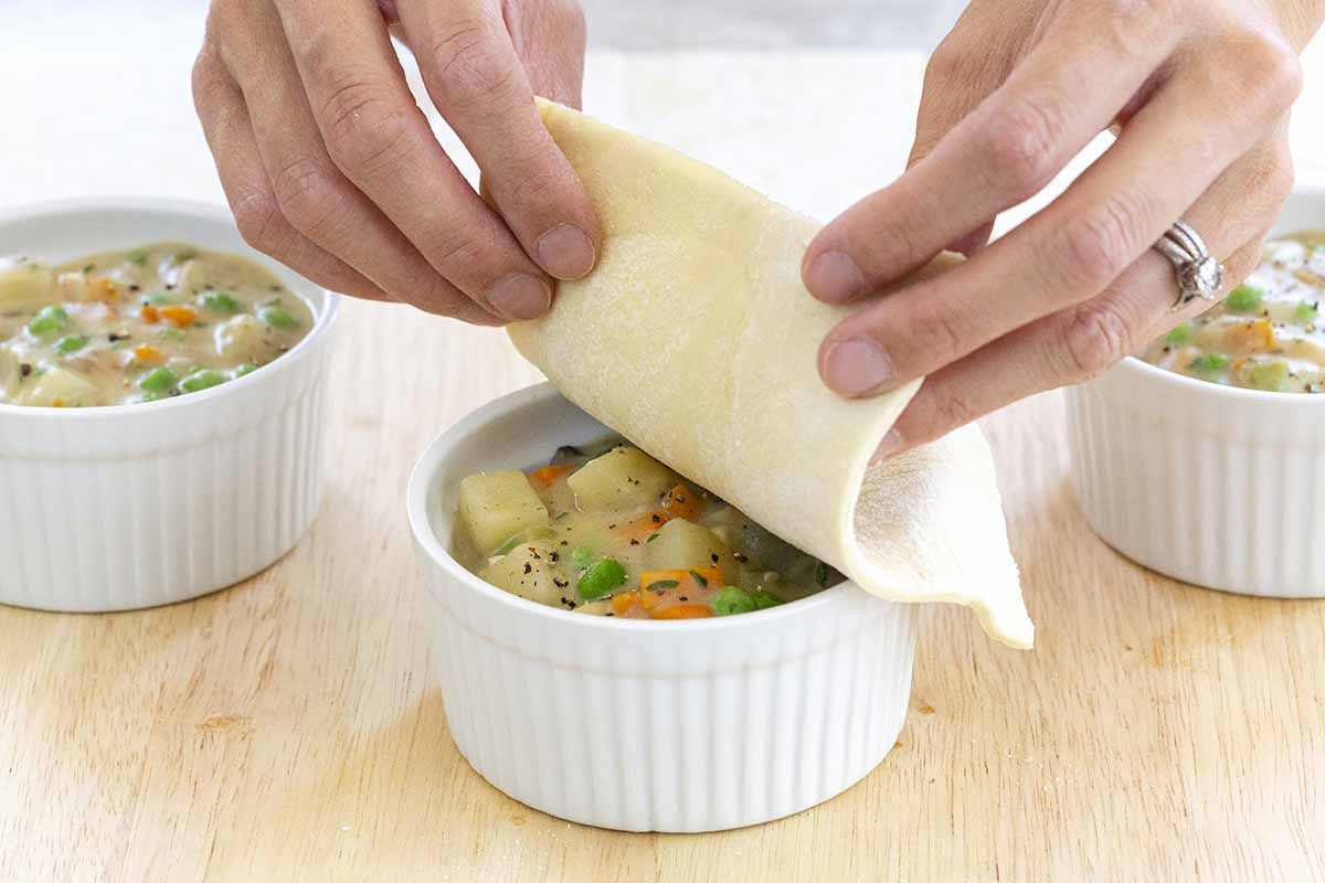 Puff pastry sheets being placed on top vegetarian pot pies.