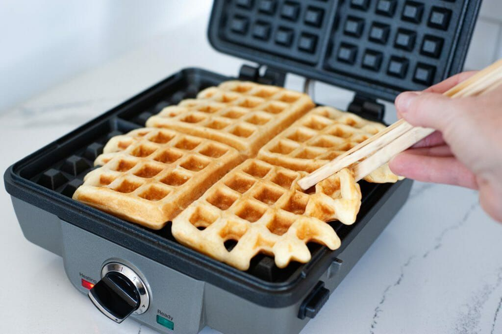 Chopsticks pulling a cooked waffle out of an open waffle maker.